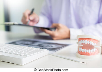 Concentrated dentist sitting at table with jaw samples tooth model in dental office professional dental clinic