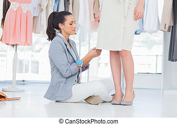 Concentrated designer picking needles on dress