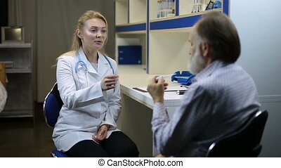 Concentrated doctor checking temperature of patient -...