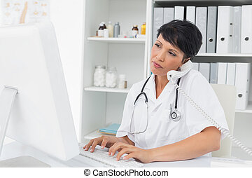 Concentrated doctor using computer and telephone - ...
