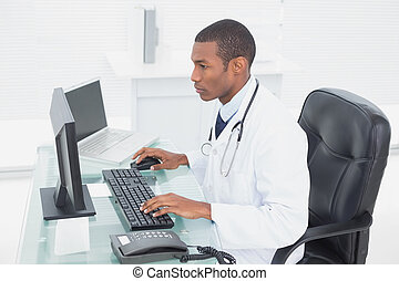 Concentrated doctor using computer at medical office - Side ...