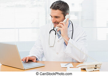 Concentrated doctor using laptop and phone - Concentrated...