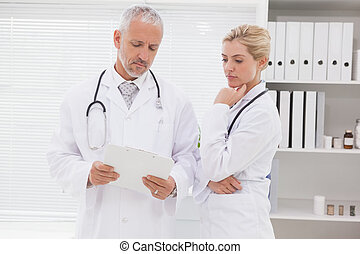 Concentrated doctors coworker analyzing results in medical ...