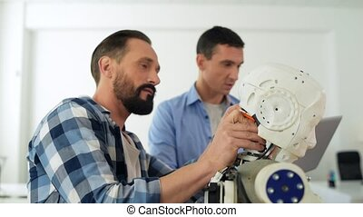 Concentrated engineers working with robot construction -...