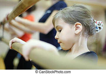 concentrated face of little girl in ballet class near frame and large mirror