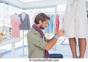 Concentrated fashion designer working on a dress