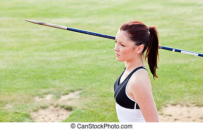 Concentrated female athlete ready to throw javelin in a...