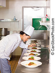 Concentrated female chef garnishing food in kitchen - Side ...