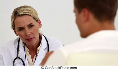 Concentrated female doctor listening to her patient sat in...