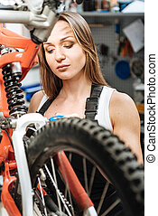 Concentrated female mechanic working in the repair shop