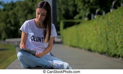 Concentrated female volunteer making notes outdoors - Do it...