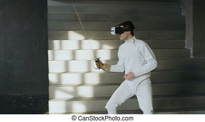 Concentrated fencer man practice fencing exercises using VR...