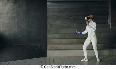 Concentrated fencer woman using virtual reality headset for...