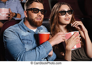 Concentrated friends loving couple sitting in cinema
