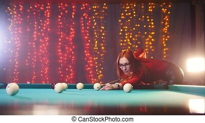 Concentrated ginger woman in red turtleneck playing billiard