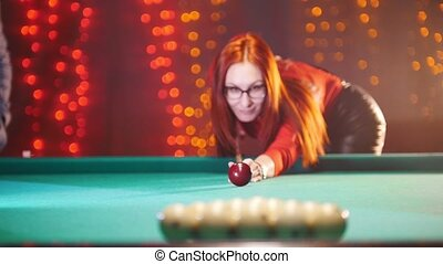 Concentrated ginger woman playing billiard in billiard club. Breaks down arranged balls