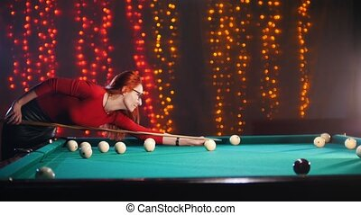 Concentrated ginger woman playing billiard in billiard club