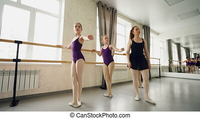 Concentrated girls are learning basic ballet positions in...