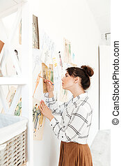 Concentrated lady fashion illustrator drawing.