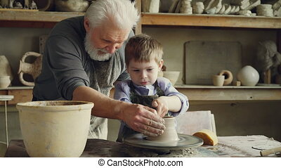 Concentrated little boy is learning to work with clay on throwing-wheel in pottery class in traditional workshop. His teacher senior experienced man is helping him.