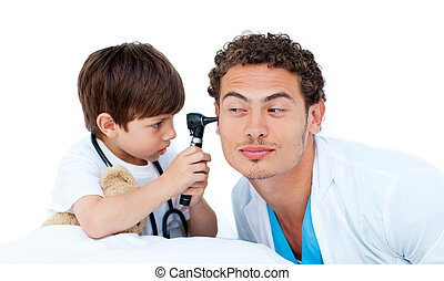 Concentrated little boy playing with the doctor