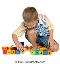 Concentrated little boy with blocks on the floor