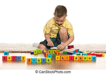 Concentrated little boy with toys on the floor