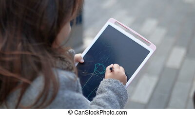 Concentrated and adorable little girl drawing stick figures on writing tablet. Cute young child doodling on tablet. Kids interacting with technology