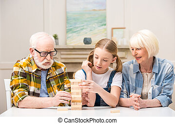 Concentrated little girl with grandparents playing jenga game together at home