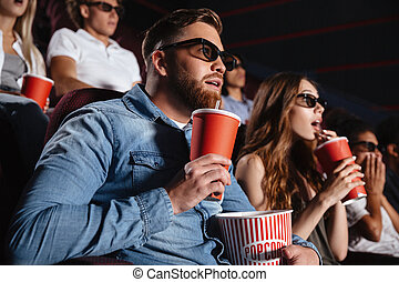 Concentrated loving couple friends sitting in cinema