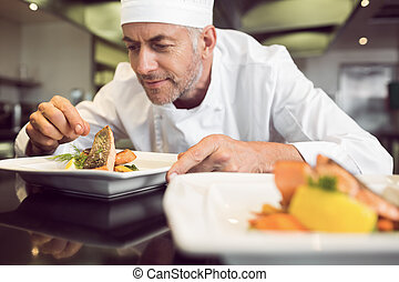 Concentrated male chef garnishing f
