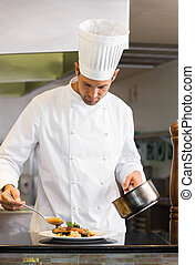Concentrated male chef garnishing food in kitchen
