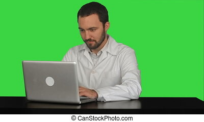 Concentrated male doctor using laptop at medical office on a Green Screen, Chroma Key