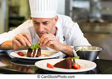 Concentrated male pastry chef decorating dessert in kitchen...