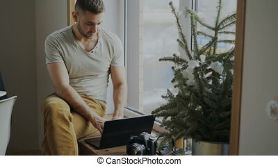 Concentrated male photographer with camera and laptop...