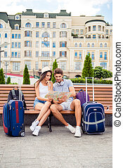 Concentrated man and woman sitting on bench and reading map