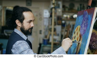 Concentrated man artist painting still life picture on...