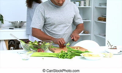 Concentrated man cutting vegetables with his girlfriend in...
