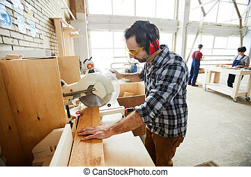 Serious concentrated handsome middle-aged man in ear protectors and protective goggles standing at workbench and cutting wooden piece with circular saw