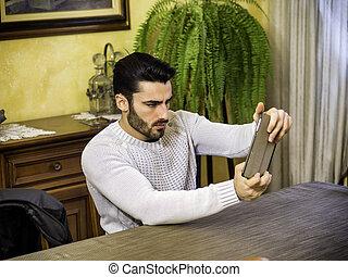 Concentrated man playing with tablet PC