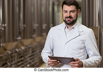 Concentrated man posing with tablet in brewery