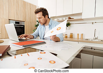 Concentrated man reprinting information from printouts