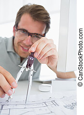 Concentrated man using compass on design