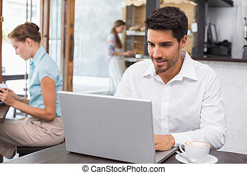 Concentrated man using laptop in coffee shop - Concentrated...
