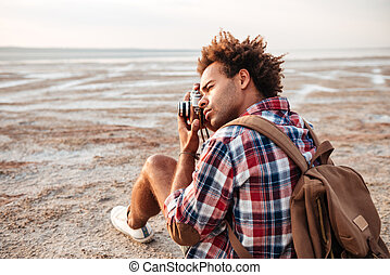 Concentrated man with backpack sitting and taking pistures...