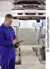 Concentrated mechanic holding a clipboard