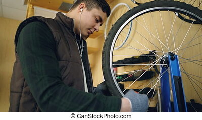 Concentrated mechanic is fixing spokes on bicycle wheel with...