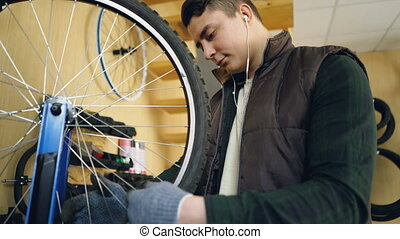Concentrated mechanic is looking at rotating bicycle wheel...