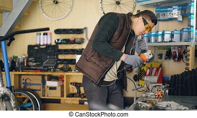 Concentrated mechanic is sawing metal part with electric...