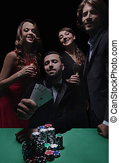 concentrated men and women playing poker in casino